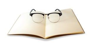 Openned brun anteckningsbok och isolerade ögonexponeringsglas arkivbilder