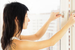 She opens a window. Beautiful woman opens a window Stock Photo
