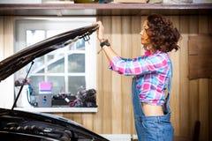 Opent de vrouwen autowerktuigkundige in denimoverall of sluit de kap van de auto royalty-vrije stock foto's