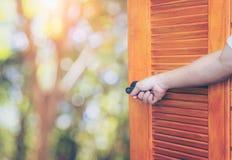 Opent het open de deurhandvat van de mensenhand de schommelende schacht of lege ruimtedeur voor aard en gele bloemgebied en blauw stock afbeelding