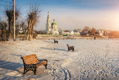 Openwork benches. On the shore of a frozen river and the monastery Royalty Free Stock Image
