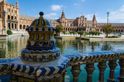 An openwork ceramic fence of the Plaza of Spain, Plaza de Espa. In the foreground is a bright, openwork ceramic fence in the traditional Spanish style, in the Stock Photography