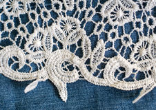 Openwork fabric lace border on denim background. Openwork fabric lace border on denim. Good as background stock image