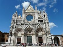 Openwork facade of the cathedral in Siena, Italy. The beautiful openwork white marble facade of the world famous Cathedral in Siena - a magnificent example of royalty free stock photo