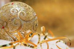 Openwork guld- jul klumpa ihop sig med bandgarneringexponeringsglas på en ljus stucken halsduk och nya Year& x27; s-begrepp, stäl Royaltyfria Foton