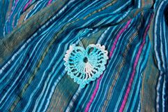 Openwork heart on a blue striped fabric Stock Image