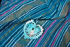 Openwork heart on a blue striped fabric Stock Photo