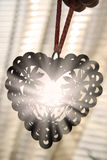 Openwork heart with sunlight rays. Hand holding openwork heart against  window with sunlight rays Royalty Free Stock Images
