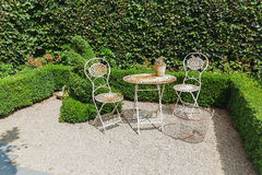 Openwork iron garden furniture to the background of the hedge Stock Photo
