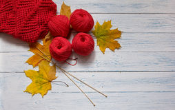 Openwork knitting, yarn, needles and fallen yellow leaves. Red yarn, wooden knitting needles, openwork knitting and yellow leaves are on white vintage wooden Stock Photography
