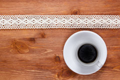 Openwork lace and cup of coffee. Openwork lace on the wooden surface and a cup of coffee Royalty Free Stock Images