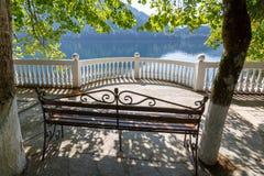 Openwork metal ławka na kurenda balkonie na brzeg malowniczy jeziorny Ritsa, Abkhazia, Gruzja na spokojnym lecie da zdjęcia stock