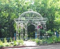 Openwork metal arbor in the garden Stock Photography