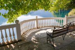 Openwork metal bench on a semi-circular balcony on the shore of the picturesque lake Ritsa, Abkhazia, Georgia on a quiet summer da. Y Royalty Free Stock Image