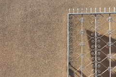 Openwork metal gate on a background of a wall Royalty Free Stock Photos