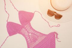 Openwork pink swimsuit, hat and sunglasses. Beach wardrobe. Fashionable concept stock photo