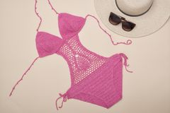 Openwork pink swimsuit, hat and sunglasses. Beach wardrobe. Fashionable concept stock photography