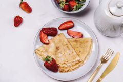 Openwork thin cheese crepes served with strawberry. On grey concrete background. Homemade pancakes. Delicious breakfast Royalty Free Stock Photo