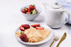 Openwork thin cheese crepes served with strawberry on grey concrete background stock photos