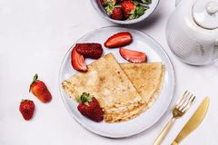 Openwork thin cheese crepes served with strawberry on grey concrete background royalty free stock photography