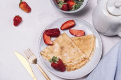 Openwork thin cheese crepes served with strawberry. On grey concrete background. Homemade pancakes. Delicious breakfast. Haze effect Royalty Free Stock Photos