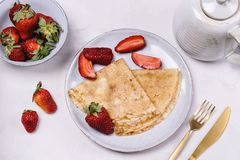 Openwork thin cheese crepes served with strawberry. On grey concrete background. Homemade pancakes. Delicious breakfast Royalty Free Stock Images