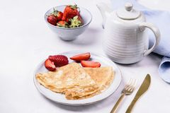 Openwork thin cheese crepes served with strawberry. On grey concrete background. Homemade pancakes. Delicious breakfast Stock Photo