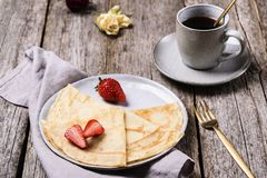 Openwork thin cheese crepes served with strawberry on wooden background royalty free stock images