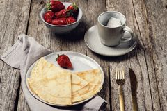 Openwork thin cheese crepes served with strawberry on wooden background stock images