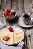 Openwork thin cheese crepes served with strawberry on wooden background stock photos