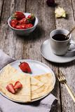 Openwork thin cheese crepes served with strawberry on wooden background royalty free stock photo