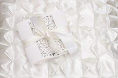 Openwork wedding invitation on a white satin background Stock Images