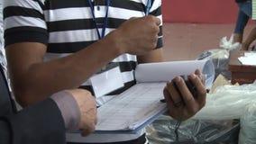 Operários do vestuário de matéria têxtil: Mão do supervisor do CU que gesticula com prancheta video estoque