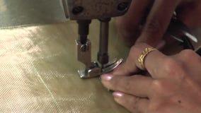 Operários do vestuário de matéria têxtil: Mãos fêmeas do CU que costuram uma parte na máquina video estoque