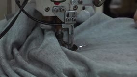 Operários do vestuário de matéria têxtil: Tela do impulso da mão do trabalhador do CU na máquina de costura filme