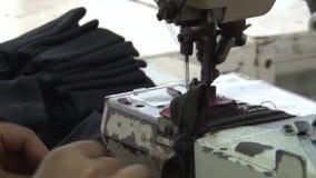 Operários do vestuário de matéria têxtil: A tela escura do CU remenda na máquina de costura filme