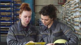 Operários fêmeas que examinam originais junto no armazenamento video estoque