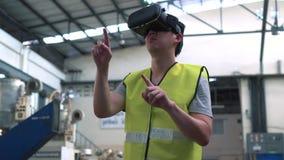 Oper?rio industrial que veste os ?culos de prote??o de VR que tocam no mundo da realidade virtual dentro da f?brica video estoque