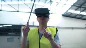 Oper?rio industrial que veste os ?culos de prote??o de VR que tocam no mundo da realidade virtual dentro da f?brica vídeos de arquivo