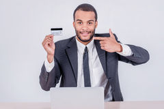 Operação bancária do Internet Homem de negócios africano bem sucedido que senta-se em um la imagens de stock