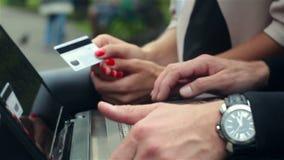 Operação bancária em linha com um portátil Mãos masculinas e fêmeas filme