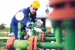 Operação da gravação do operador do processo do petróleo e gás no óleo e na planta do equipamento fotografia de stock royalty free