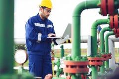 Operação da gravação do operador do processo do petróleo e gás no óleo e na planta do equipamento fotos de stock