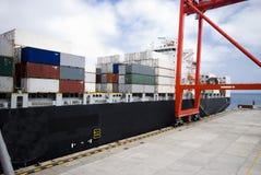 Operação do recipiente no porto com os guindastes e a carga do pórtico/os recipientes do descarregamento Fotos de Stock Royalty Free