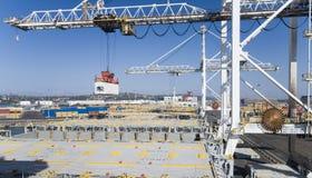 Operação do recipiente no porto com os guindastes e a carga do pórtico/os recipientes do descarregamento Fotografia de Stock
