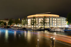 The opera building at night in the center of Amsterdam in the. Boats sail past the Opera House `The Opera` at night in the center of Amsterdam royalty free stock photos