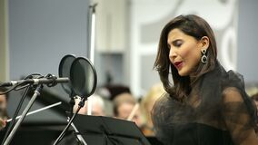 Opera singer sings in the microphone with the orchestra. Recorded the song on radio culture stock video
