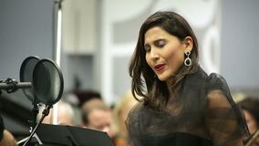 Opera singer sings in the microphone with the orchestra. Recorded the song on radio culture stock video footage