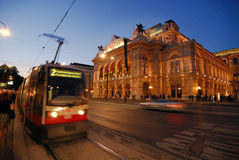 Opera of Vienna. View of the illuminated Opera building of Vienna at dusk including a tram royalty free stock images