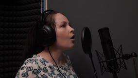 Opera vrouwelijke zanger die dramatisch lied zingen Het emotionele uitvoeren van lied Jong Kaukasisch meisje die bij opnamestudio stock videobeelden